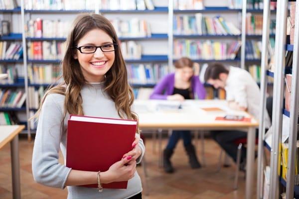 Junge Studentin, die lächelt beim Spanisch lernen