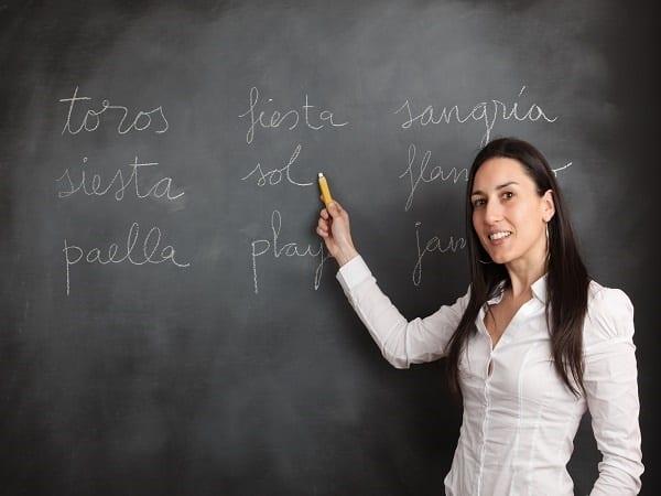 Woman showing spanish topics on a blackboard.